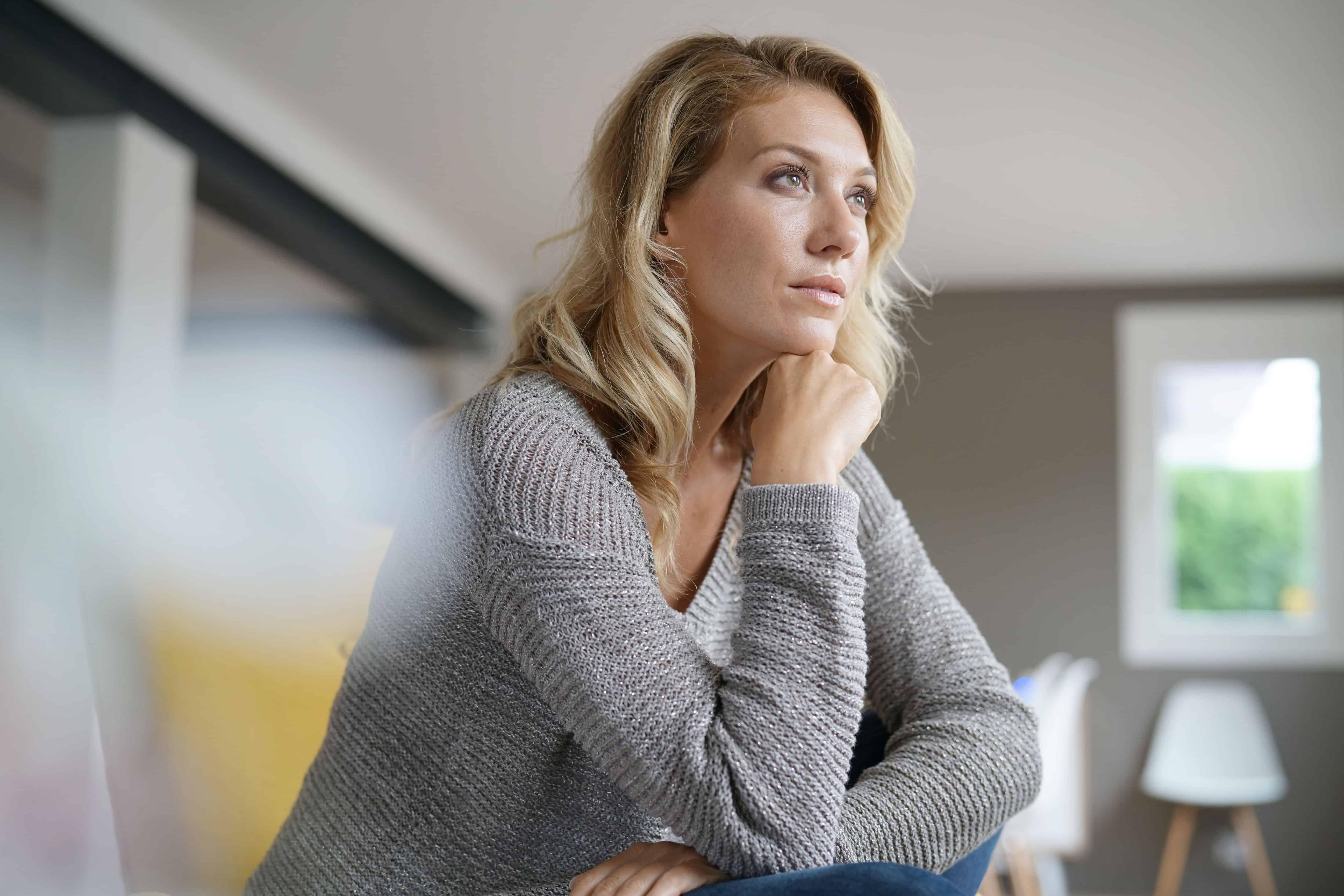 Eine attraktive Blondine sitzt im Haus und denkt nach