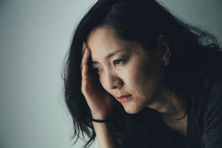 Eine besorgte Chinesin schaut in die Ferne