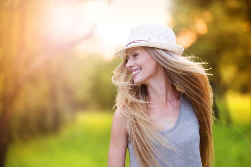 Eine glückliche Blondine mit weißem Hut genießt einen Spaziergang an einem sonnigen Tag