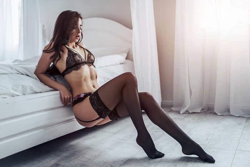 Eine hübsche Frau in sexy Dessous posiert neben den Betten