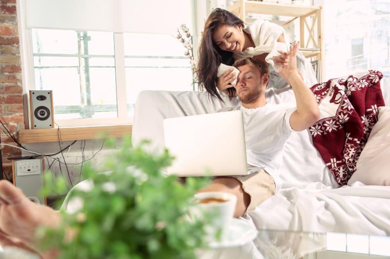 Eine lächelnde Frau wischt sich den Schweiß von der Stirn ihres Mannes, während er an seinem Laptop arbeitet