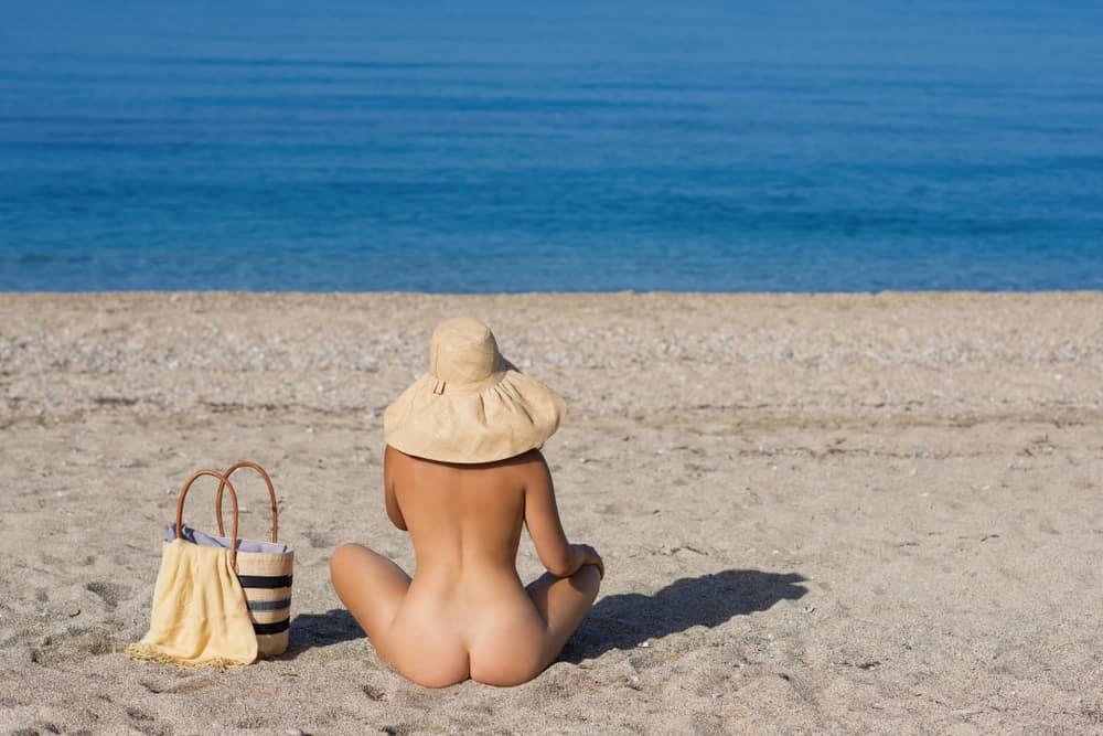Eine nackte Frau mit einem Hut auf dem Kopf sitzt am Strand