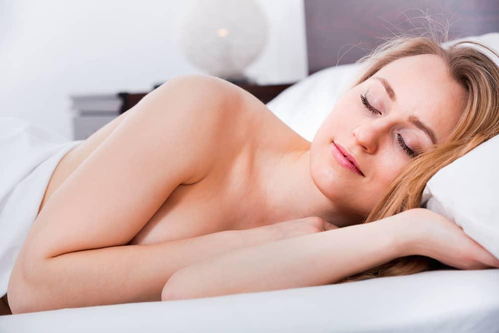 Eine nackte Frau schläft mit einem Lächeln im Gesicht