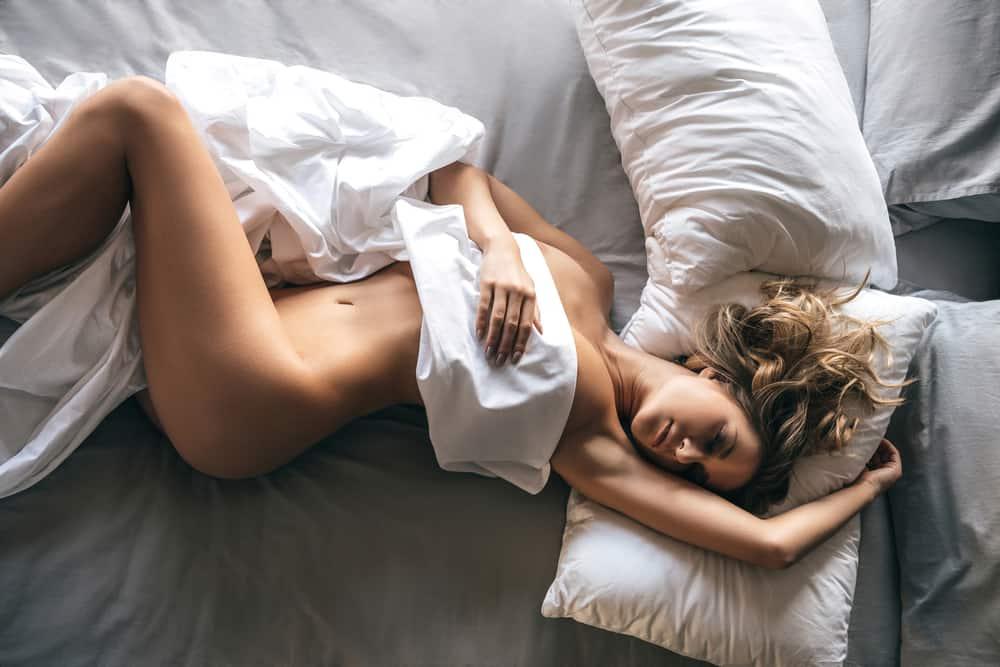 Eine nackte hübsche Frau schläft unter einem weißen Laken