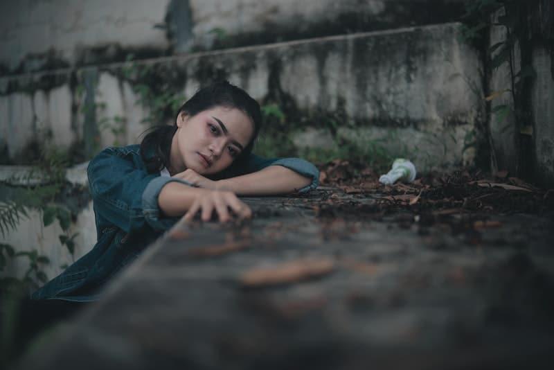 Eine traurige Chinesin sitzt auf einer konkreten Tribüne