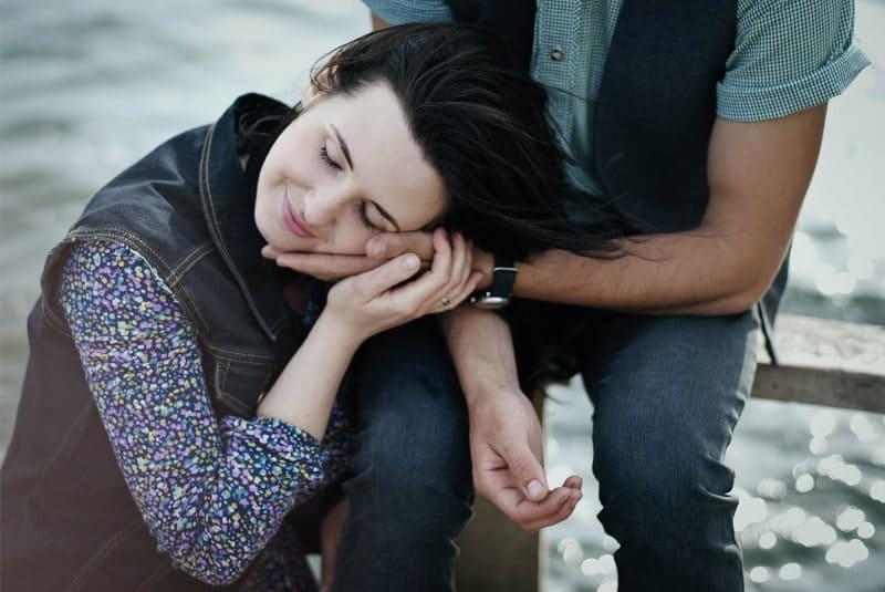 Eine zufriedene Frau hält ihren Kopf in der Hand eines Mannes