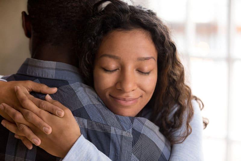 Eine zufriedene Frau umarmt ihren Mann
