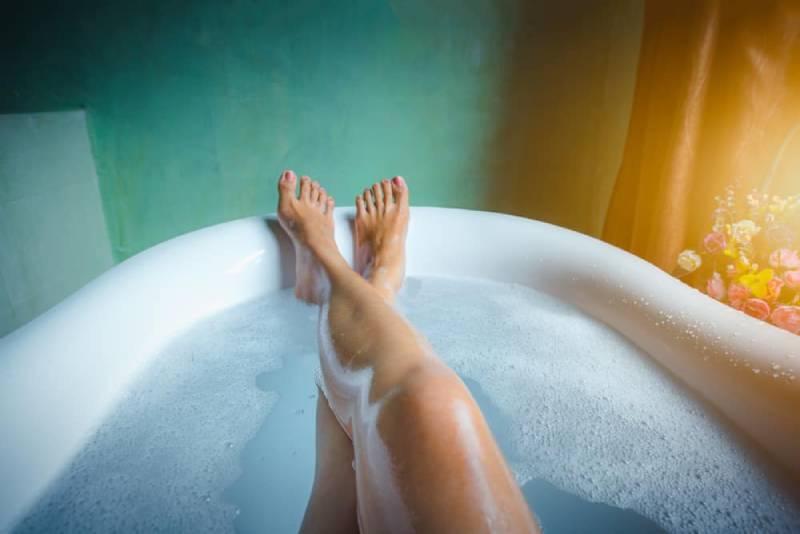 Füße mit rotem Nagellack in der Badewanne