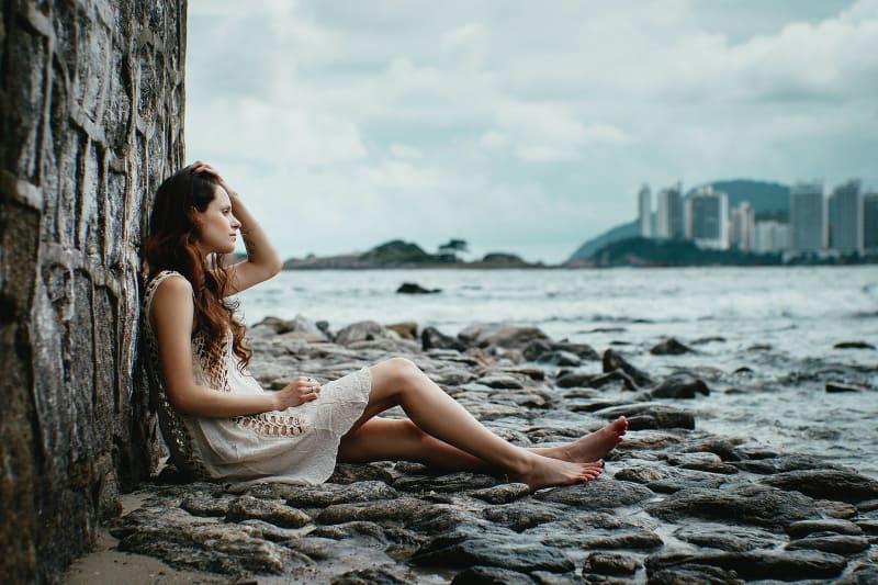 Frau, die sich auf Steinmauer nahe Gewässern stützt(1)