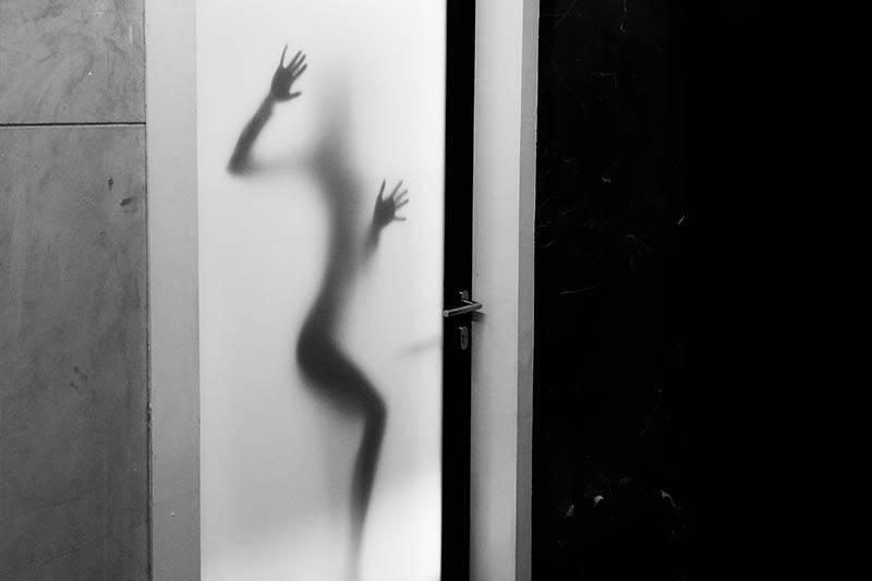 Frauenkörper auf verschwommenem Glas an der Tür