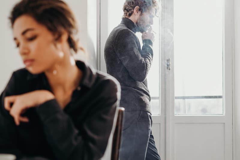 Hinter der traurigen Frau steht ein Mann, der eine Zigarette raucht