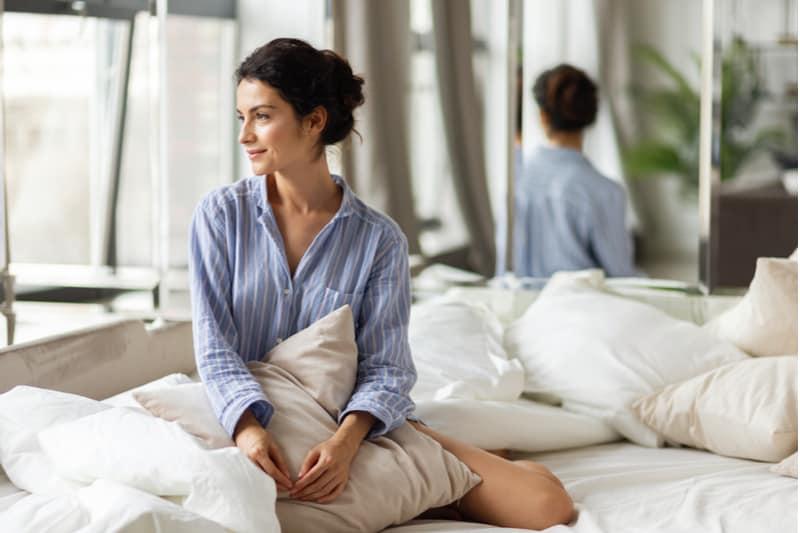 Im Doppelbett sitzt eine attraktive lächelnde Brünette und schaut aus dem Fenster