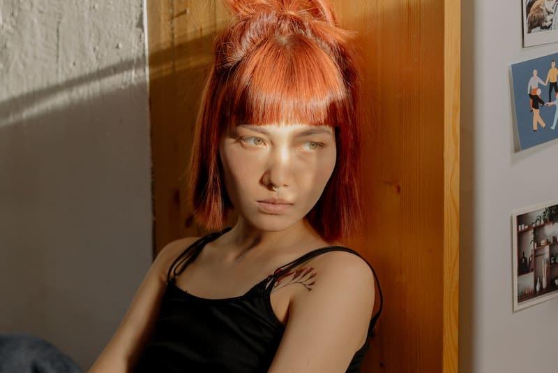 Im Haus auf dem Boden sitzt eine traurige rothaarige Frau