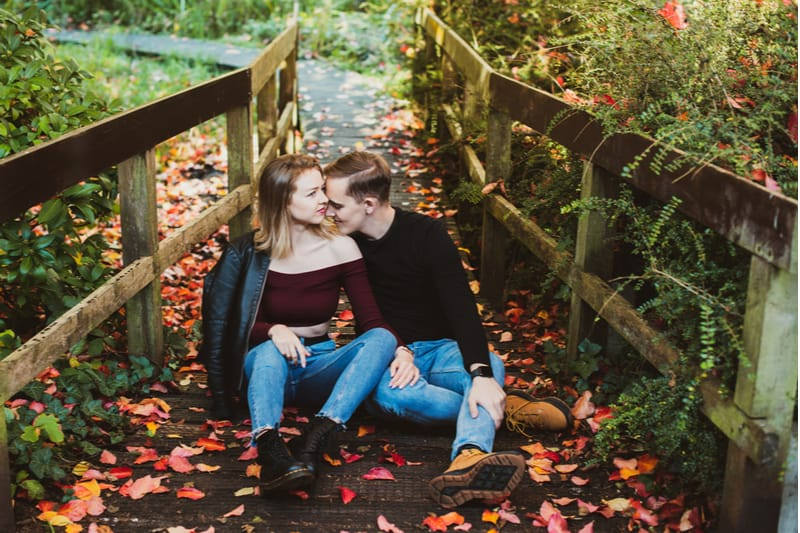 Im Herbst sitzt ein Liebespaar im Wald