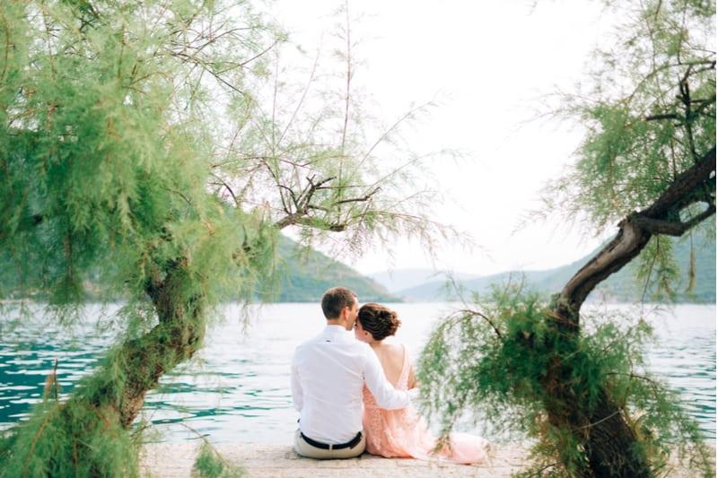 In der Nähe des Sees sitzt in einer Umarmung ein liebevolles Paar