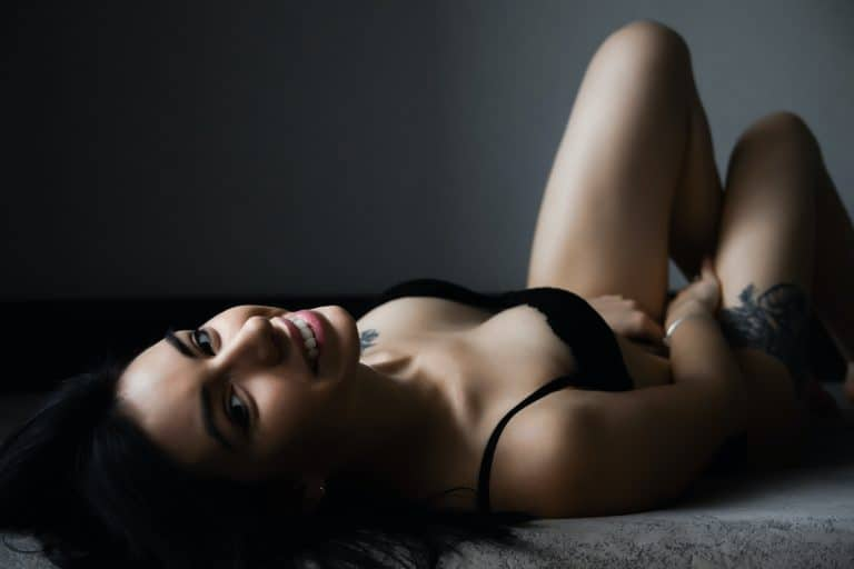 Mädchen in schwarzen sexy Dessous liegt auf dem Bett und lacht