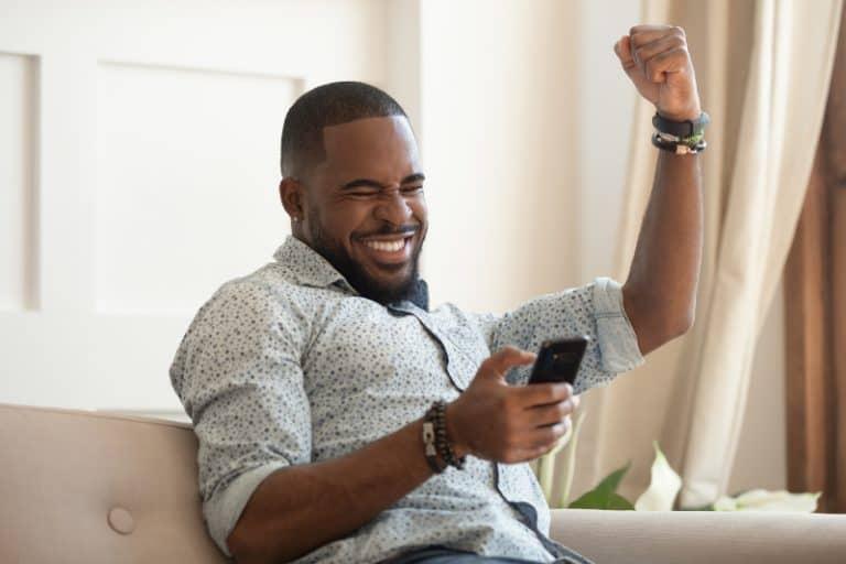 Mann Gewinner hält Smartphone