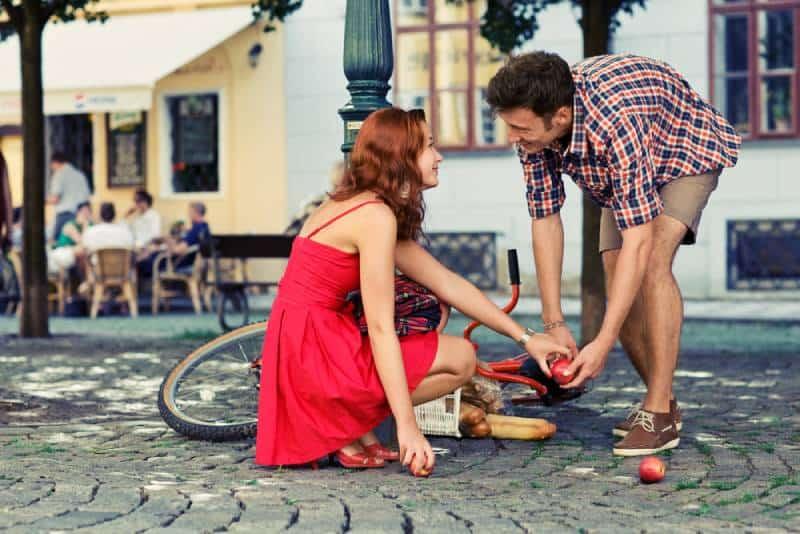Mann hilft Mädchen, das vom Fahrrad fiel
