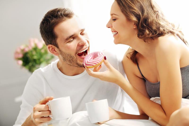 Morgenkaffee mit den Süßigkeiten eines liebenden Paares im Bett