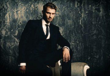 Ein Mann in einem Anzug, der sich gegen einen Sessel lehnt