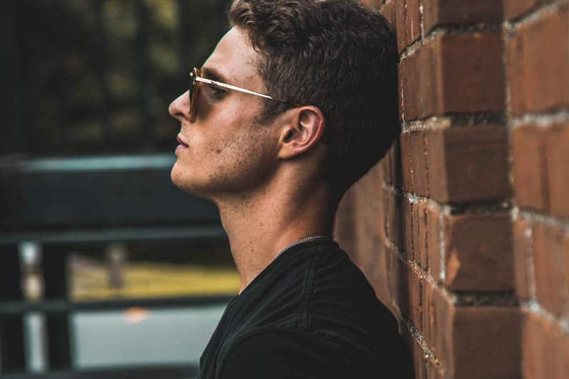 Seitenansicht des Mannes mit Sonnenbrille, die auf Wandziegel lehnt