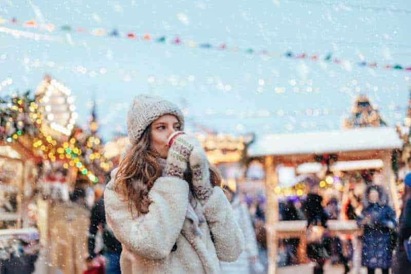 Das Mädchen draußen im Schnee trinkt ein heißes Getränk