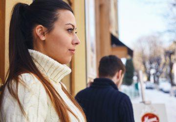 Mädchen, das vor dem Café steht, wegschaut und ein Junge, der im Hintergrund weggeht.