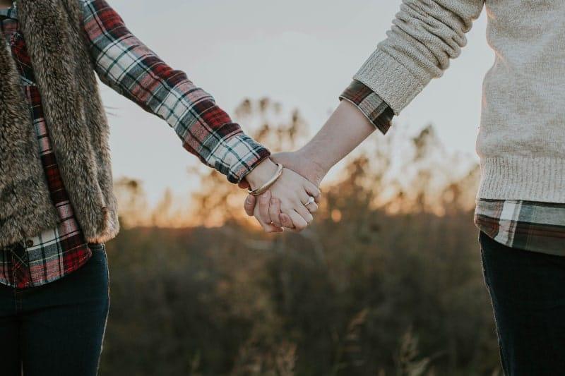 Verlobte halten draußen die Hände