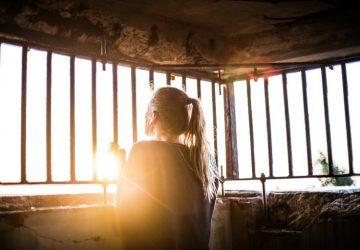 ein junges Mädchen, das hinter Gittern steht