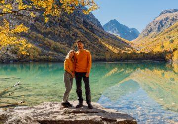 Auf einem Felsen am See steht ein liebevolles Paar