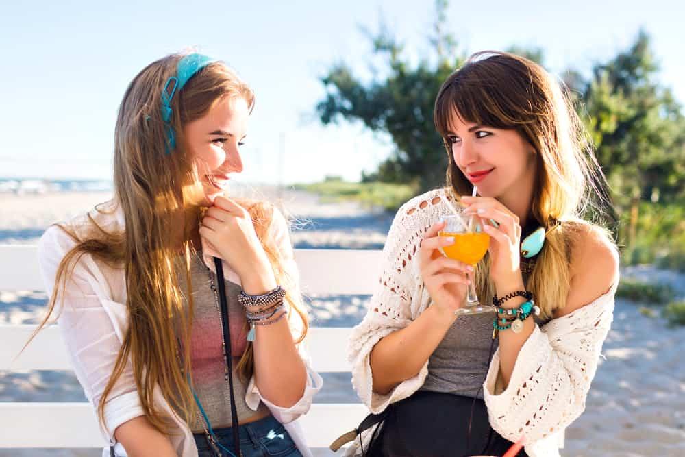 Zwei Freunde sitzen draußen und trinken und unterhalten sich mit einem Lächeln