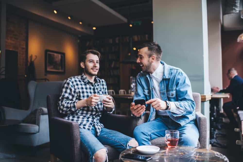 Zwei Männer sitzen in einem Café und reden und lachen