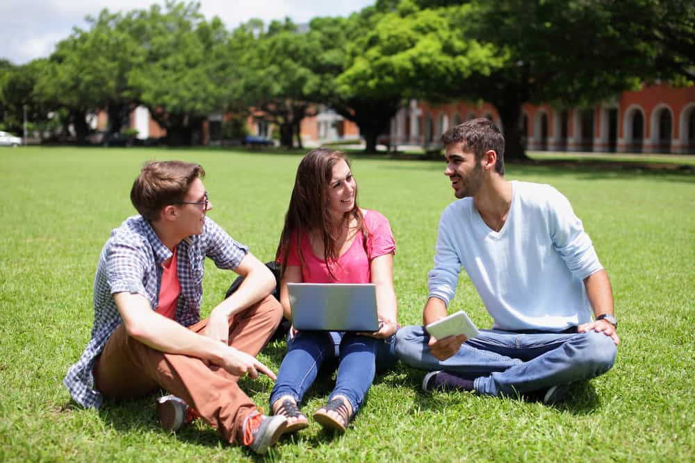 Zwei Männer und ein Mädchen sitzen im Gras und scherzen