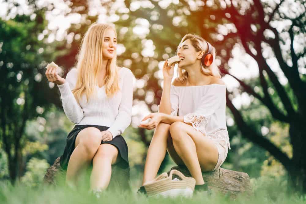 Zwei attraktive Blondinen sitzen im Park und essen und reden