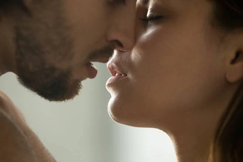 ein Kuss einer Brünetten und eines Mannes mit Bart