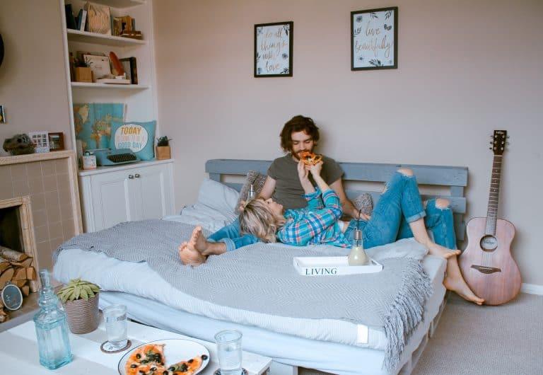 ein Mädchen, das im Bett liegt und ihrem Freund eine Pizza gibt