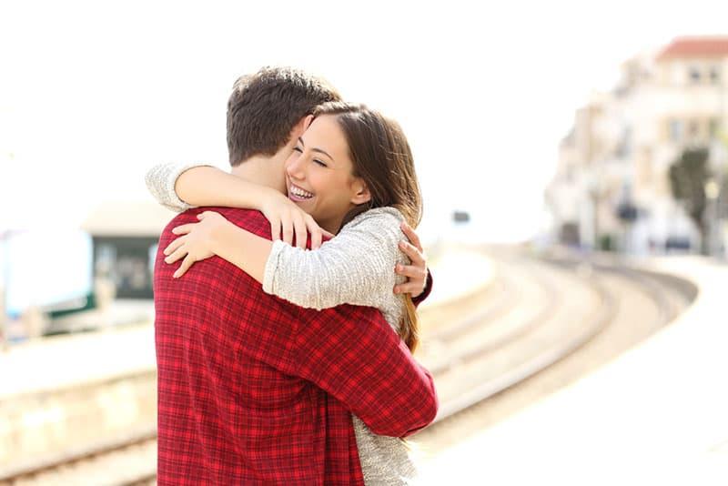 ein Mann und eine Frau in einer Umarmung auf einer Eisenbahn
