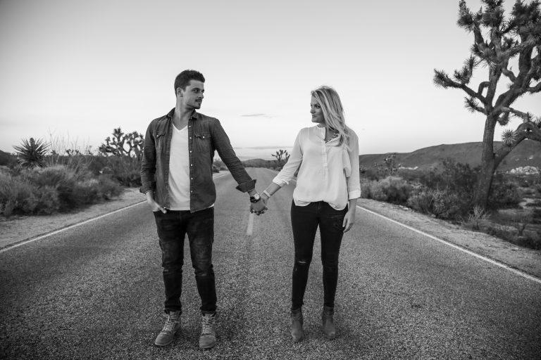 ein Paar, das mitten im Häufigen steht und Hände hält