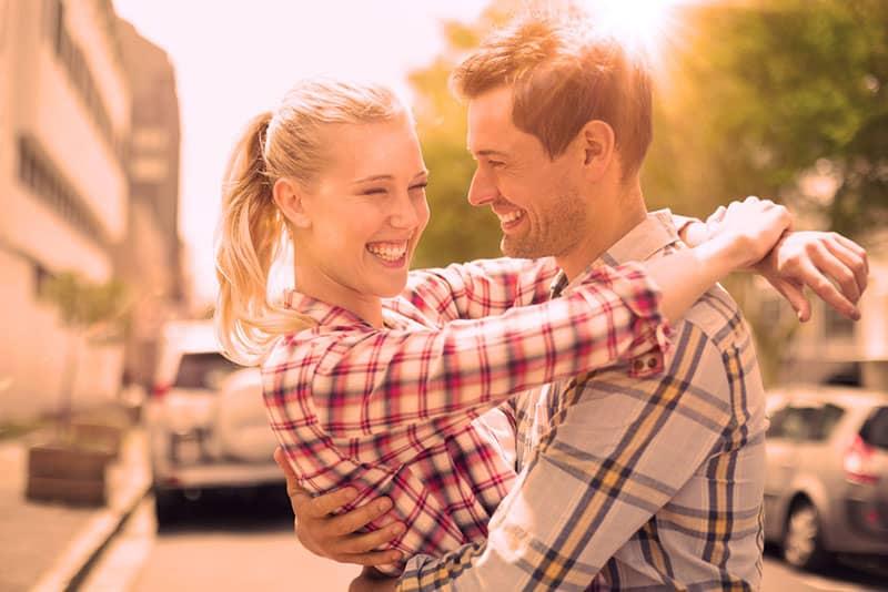 ein glückliches Paar auf der Straße steht umarmend