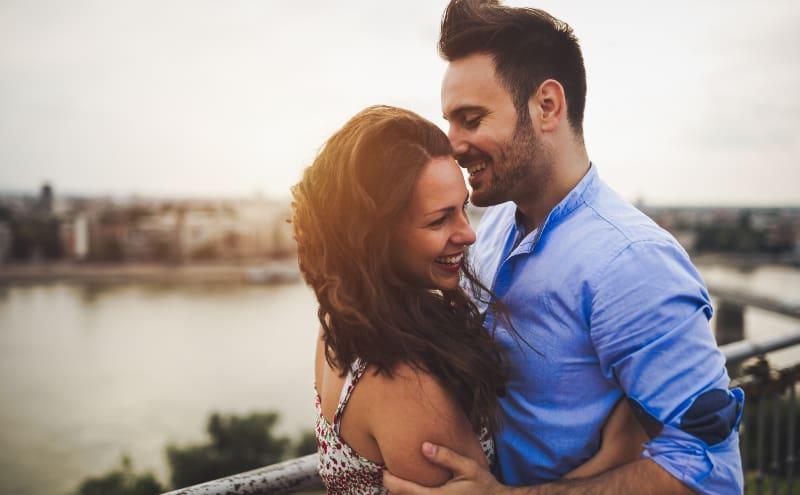 ein lächelndes Liebespaar in einer Umarmung auf einer Terrasse über dem Fluss