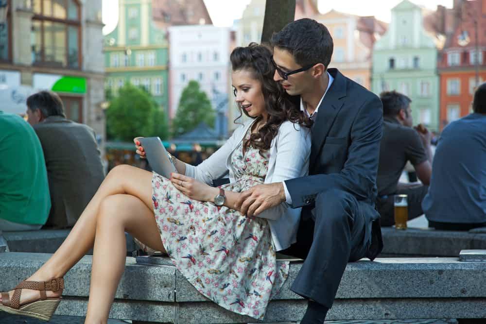 ein liebendes Paar, das draußen in der Stadt sitzt und eine Tablette benutzt