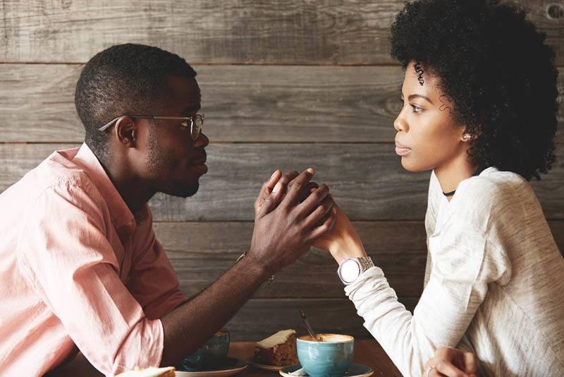 ein liebendes Paar sitzt mit Kaffee Händchen haltend