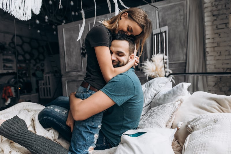 ein liebevolles Paar in einer starken Umarmung auf einem Doppelbett