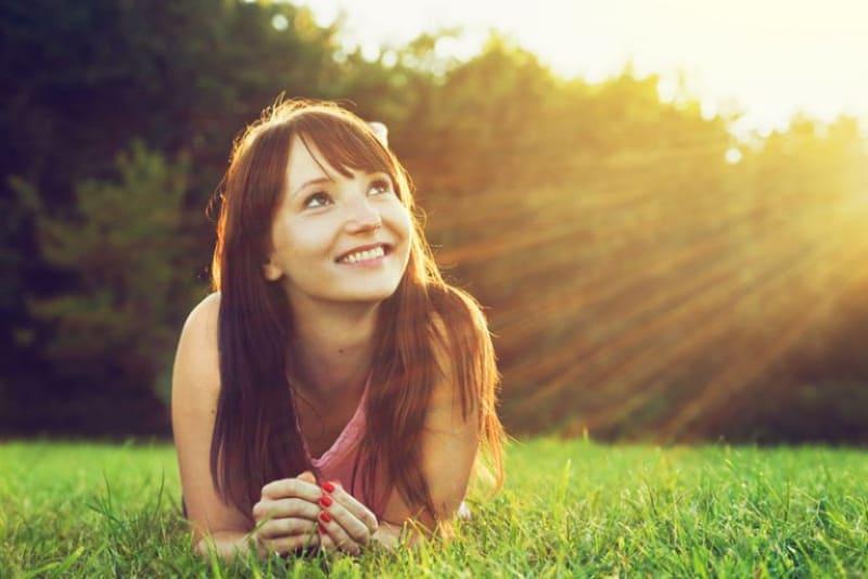 ein schönes junges Mädchen, das einen sonnigen Tag genießt, während sie im Gras liegt