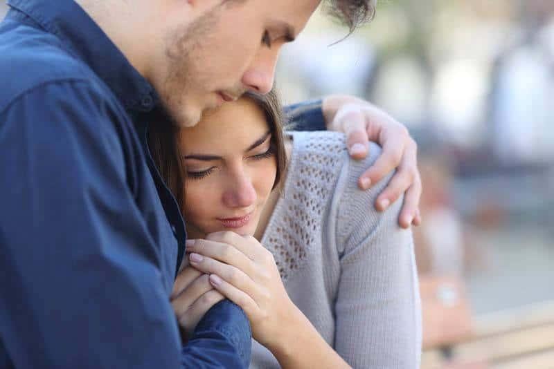 ein trauriges Liebespaar in einer Umarmung, das auf einer Bank sitzt