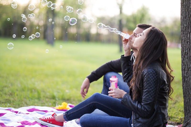 eine Frau, die mit ihrem Mann im Gras im Park sitzt und Blasen bläst