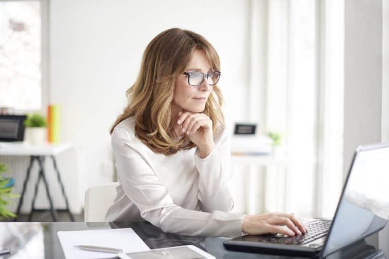 eine Frau mittleren Alters, die an einem Laptop arbeitet