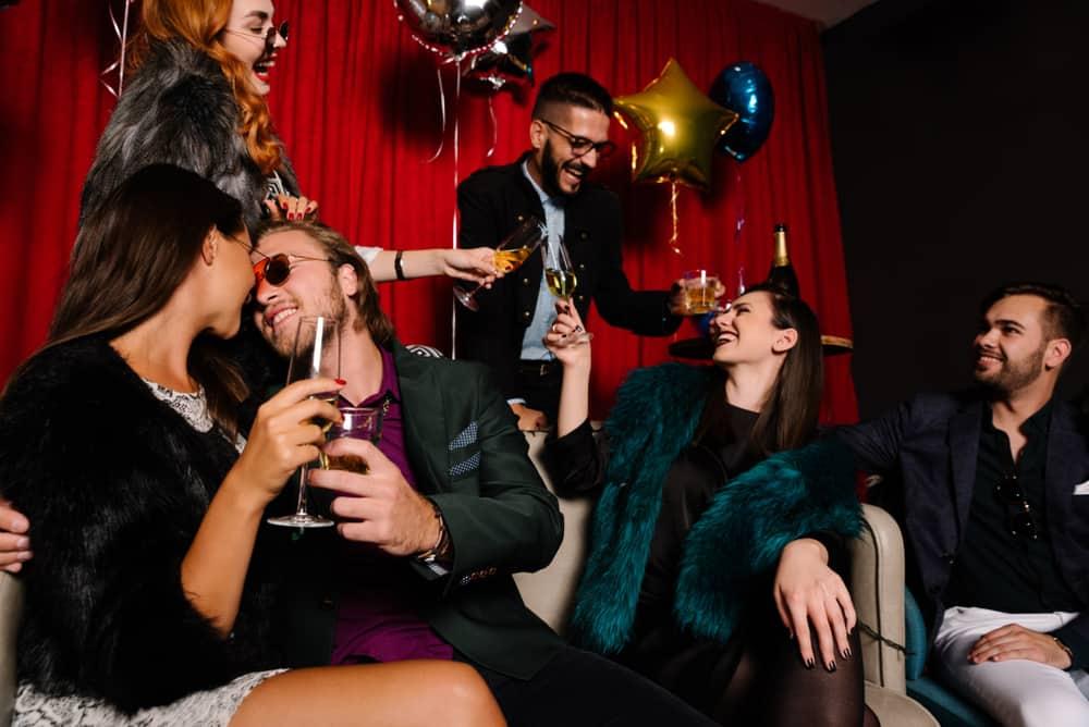 eine Gruppe von Swingern auf einer Party, die sich beide küssen