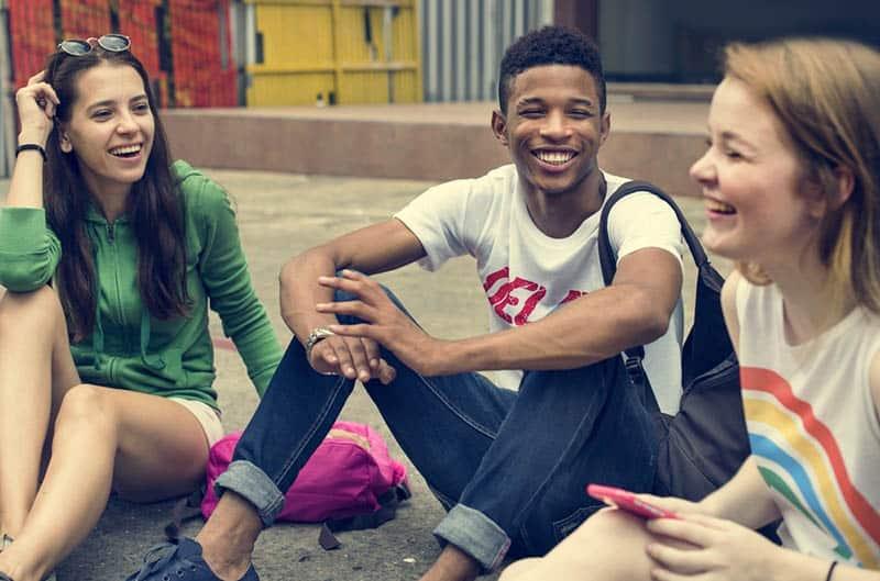 eine lächelnde Gruppe von Teenagern, die auf dem Asphalt sitzen