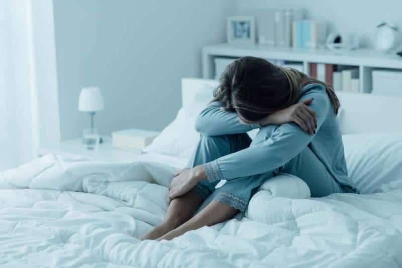 eine traurige Frau im blauen Pyjama, die auf dem Bett sitzt